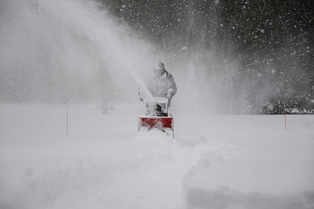 Snow Removal-A person clearing up snow from a path.